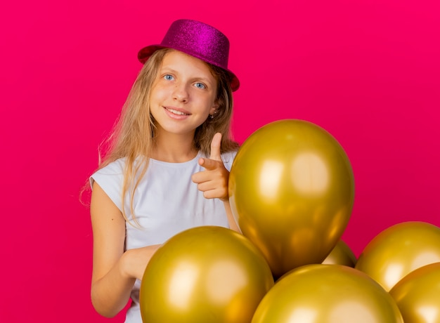 Cheerful pretty little girl in holiday hat with bunch of baloons smiling pointing with index finger at camera, birthday party concept standing over pink background Free Photo