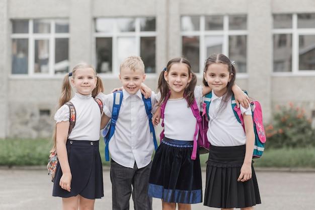 Веселые ученики, стоящие возле школы Premium Фотографии