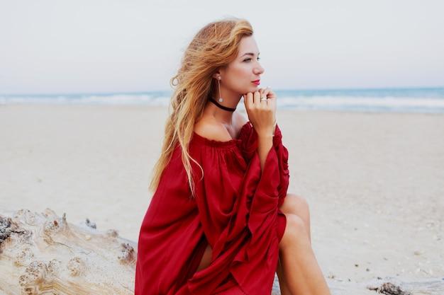 陽気な赤い頭の女の子がビーチでポーズします。白い砂の上に座っています。風の強い髪。トレンディな服。ライフスタイルの肖像画。旅行気分。海の海岸。 無料写真