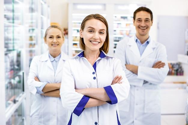 Веселые надежные три фармацевта, скрестив руки, готовы проконсультировать и предоставить услуги Premium Фотографии