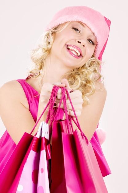 ショッピングバッグと陽気なサンタヘルパーの女の子 Premium写真