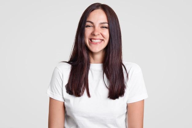 Allegra soddisfatta signora bruna ha un sorriso a trentadue denti, essendo di buon umore esprime emozioni positive Foto Gratuite