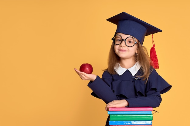 Cheerful schoolgirl in graduation outfit carrying apple while standing beside pile of textbooks Premium Photo