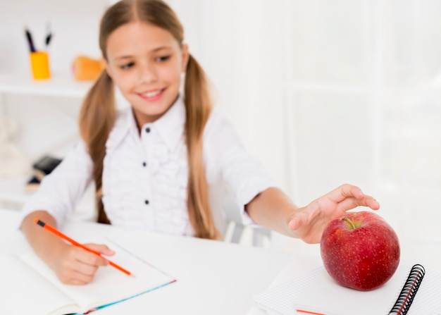 Cheerful schoolgirl smiling and taking red apple Free Photo
