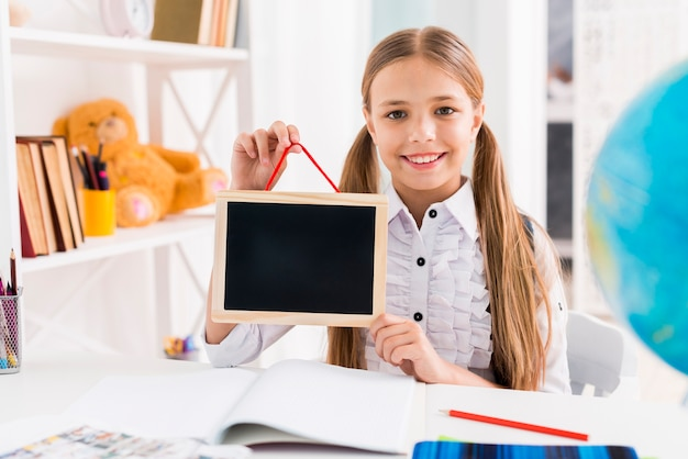 Cheerful schoolgirl in uniform studying at class Free Photo