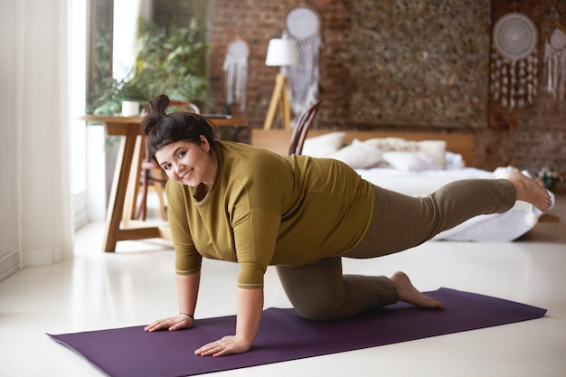 Cheerful self determined young woman with curvy body and hair knot exercising indoors on yoga mat strengthening muscles, keeping both hands and knee on floor, raising one leg and smiling joyfully Free Photo