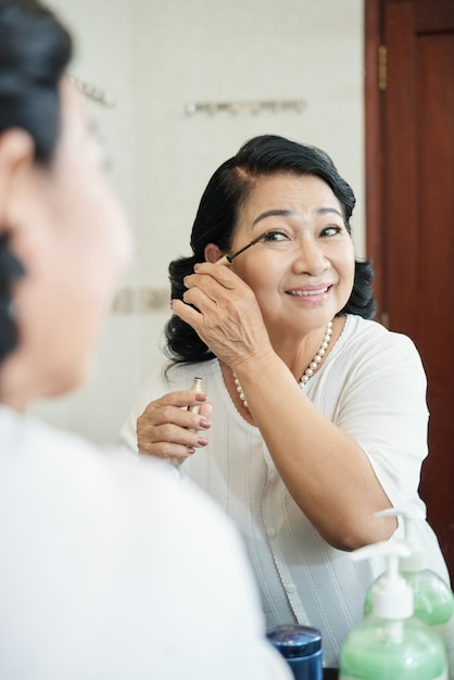 Cheerful senior asian woman putting mascara on eyelashes in front of mirror Free Photo