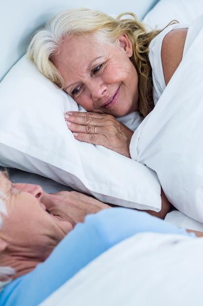 Cheerful senior couple sleeping on bed Premium Photo