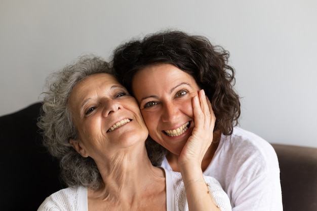 Cheerful senior mother and adult daughter posing at home Free Photo