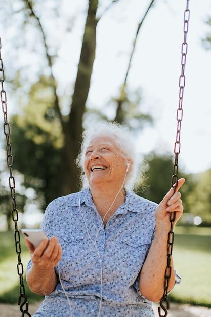 Cheerful senior woman listening to music at a playground Premium Photo