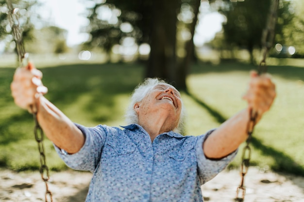 Cheerful senior woman on a swing at a playground Premium Photo