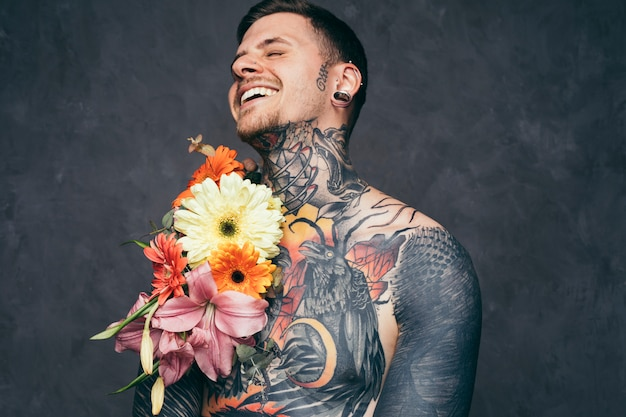 Cheerful shirtless young man with pierced ears with flower decoration on his tattooed body Free Photo