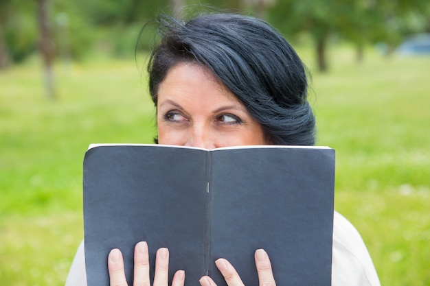 Cheerful sly woman hiding face behind open diary Free Photo