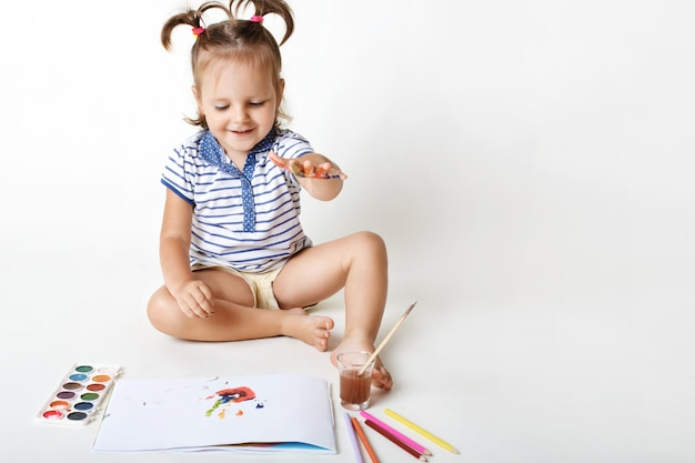 Cheerful small female kid draws with watercolour, makes fingerprints, has fun alone, likes to paint, isolated on white. creative little girl makes piece of art, being future painter Free Photo