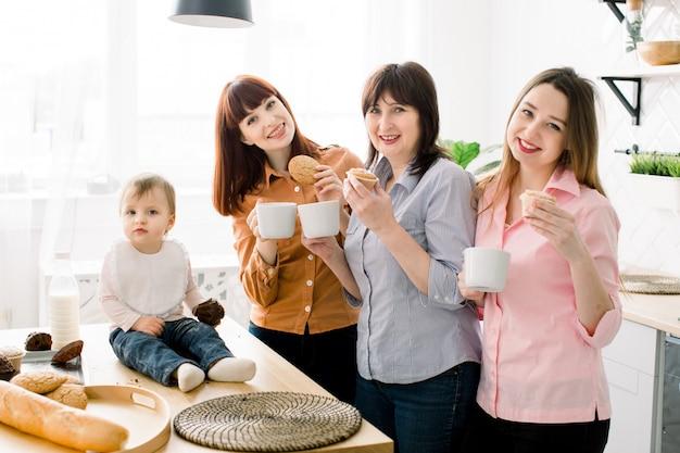 陽気な笑顔の魅力的な若い女性、中年の女性、かわいい女の子のクッキーやカップケーキを食べたり、家庭の台所でコーヒーを飲みます。幸せな母の日コンセプト、一緒に料理 Premium写真