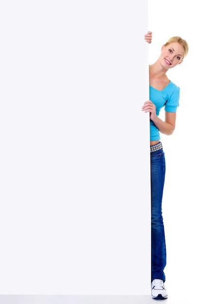 La donna bionda sorridente allegra guarda fuori a causa di un'insegna di carta vuota Foto Gratuite