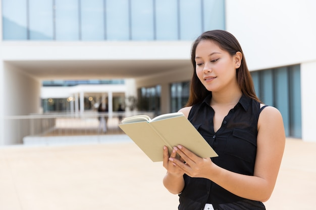 Cheerful smiling female student reading textbook Free Photo