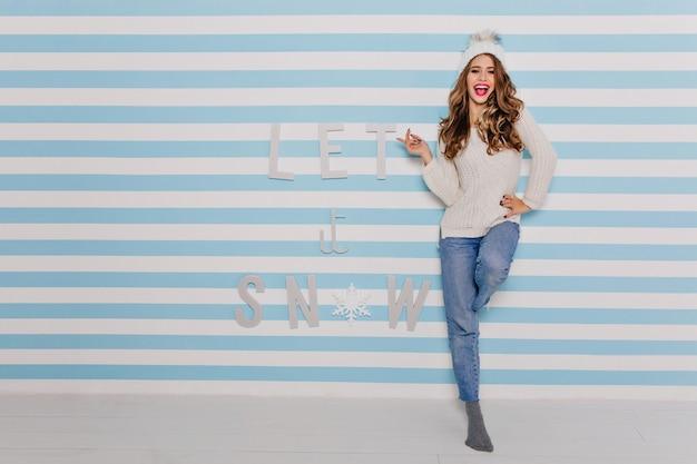 機嫌の良い陽気な笑顔の女の子は、白い縞模様の青い壁にコケティッシュにポーズをとっています。 無料写真