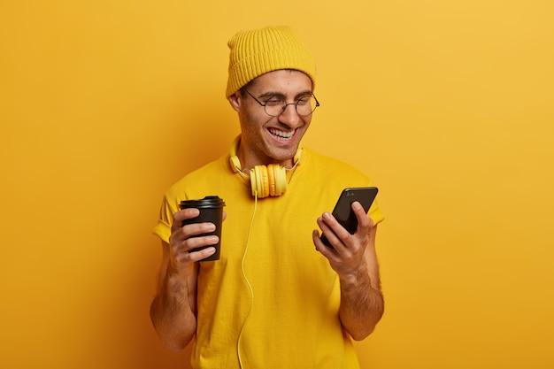 밝고 웃는 남자는 스마트 폰을 통해 재미있는 비디오를 보며 종이 컵에서 맛있는 뜨거운 음료를 마시고 노란 모자와 티셔츠를 입습니다. 무료 사진