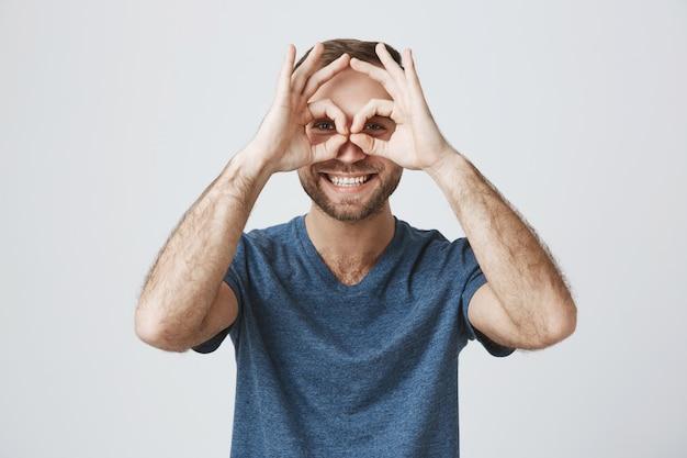 L'approvazione bella sorridente allegra di manifestazione dell'uomo bello firma sopra gli occhi Foto Gratuite