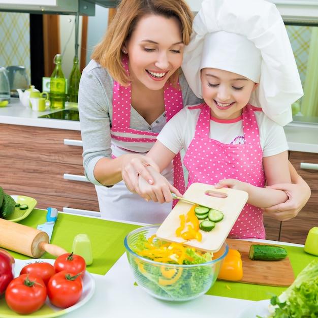 Веселые улыбающиеся мать и дочь, готовящие салат на кухне. Бесплатные Фотографии