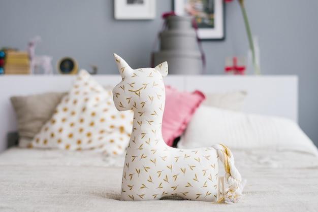 Cheerful soft unicorn toy on the bed Premium Photo