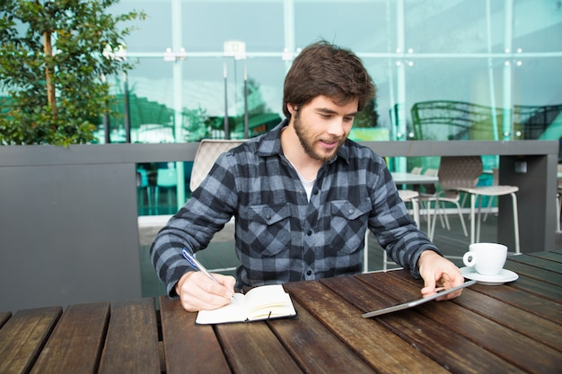 Cheerful student taking notes for essay Free Photo