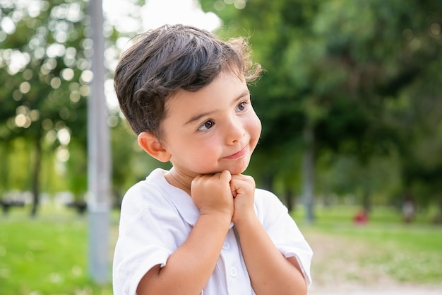 Allegro ragazzino dolce in piedi e in posa nel parco estivo, appoggiando il mento sulle mani, sorridendo e guardando lontano. colpo del primo piano. concetto di infanzia Foto Gratuite