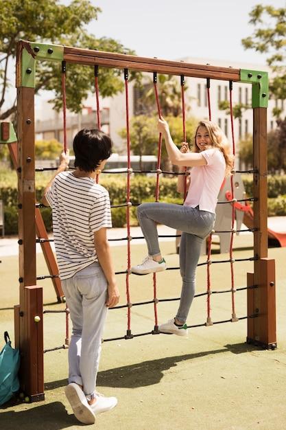 Cheerful teen friends on climbing net on playground Free Photo