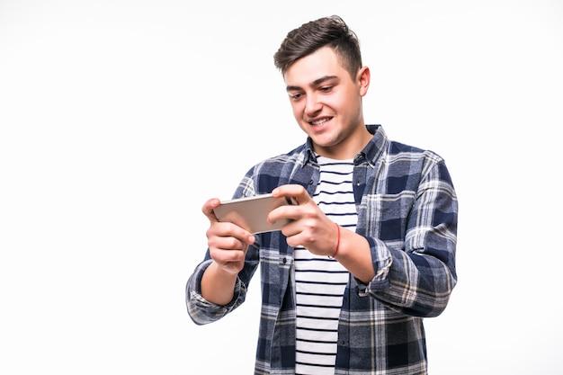 Веселый подросток играет в игры на своем мобильном телефоне Бесплатные Фотографии