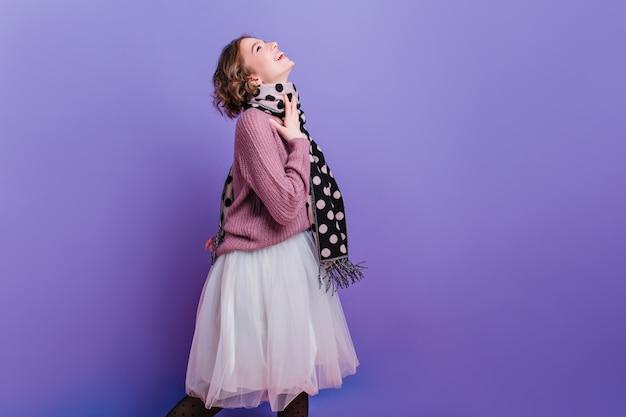 무성한 치마 포즈에서 포즈를 취하 긴 어두운 스카프로 명랑 유행 소녀 Photoshoot를 즐기는 곱슬 검은 머리와 예쁜 여성 모델의 사진. 무료 사진