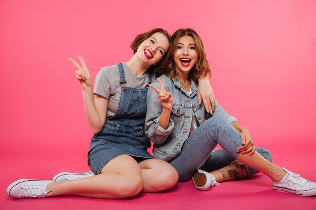 Cheerful two women friends sitting on floor Free Photo