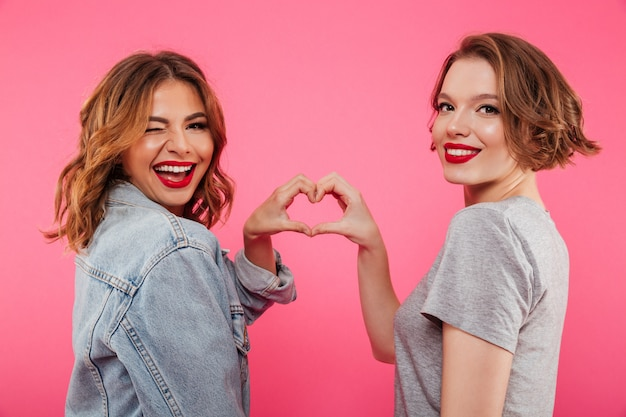 Cheerful two women hugging showing heart love gesture. Free Photo
