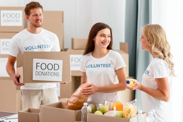 Allegri volontari che preparano provviste di cibo per le donazioni Foto Gratuite