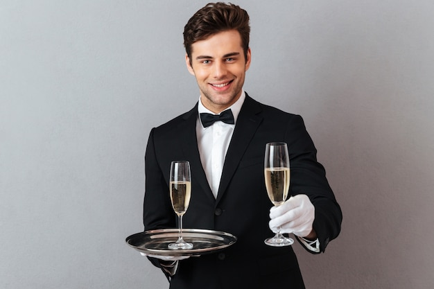 Cheerful waiter holding glass of champagne give it to you. Free Photo
