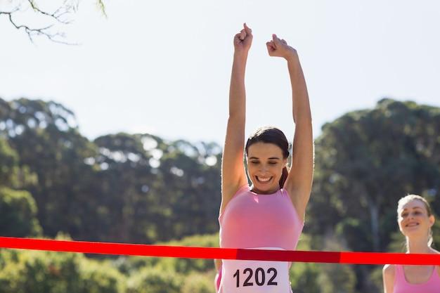 Cheerful winner athlete crossing finish line Premium Photo