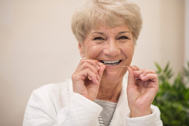Cheerful woman cleaning her teeth Free Photo
