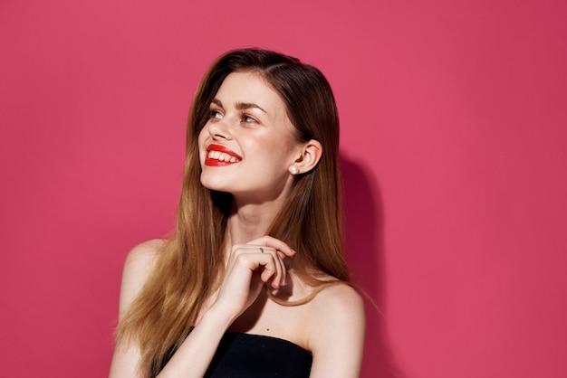 쾌활 한 여자 화장품 붉은 입술 미소 매력적인 모습 분홍색 배경. 프리미엄 사진