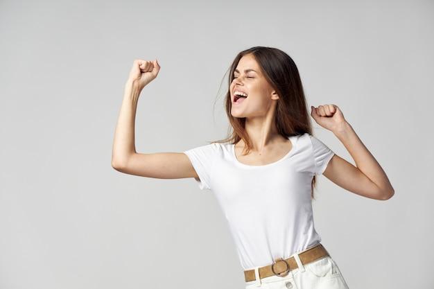 陽気な女性の感情ジェスチャー手スタジオ白いtシャツ Premium写真