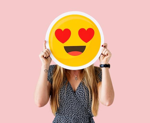 Cheerful woman holding emoticon icon Free Photo