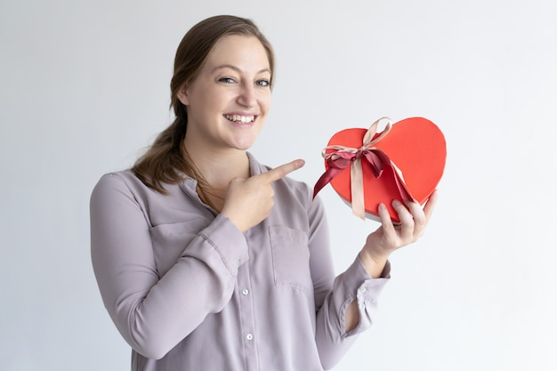 Cheerful woman holding heart shaped gift box and pointing at it Free Photo