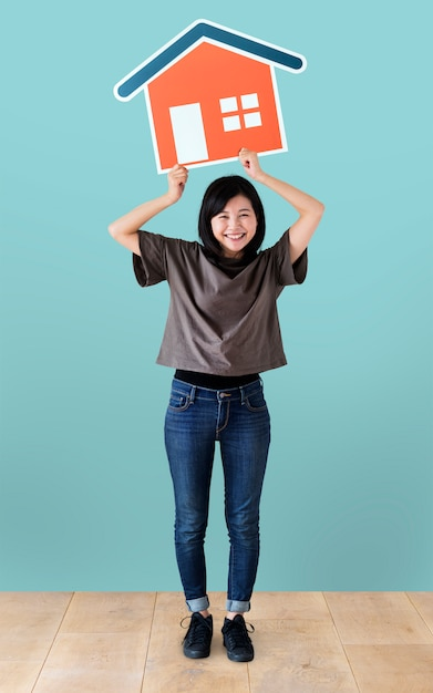 Cheerful woman holding a house icon Free Photo