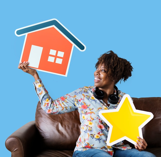 Cheerful woman holding a house and star icons Free Photo