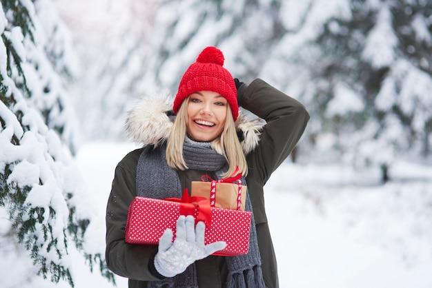 Donna allegra che tiene pila di regali di natale Foto Gratuite
