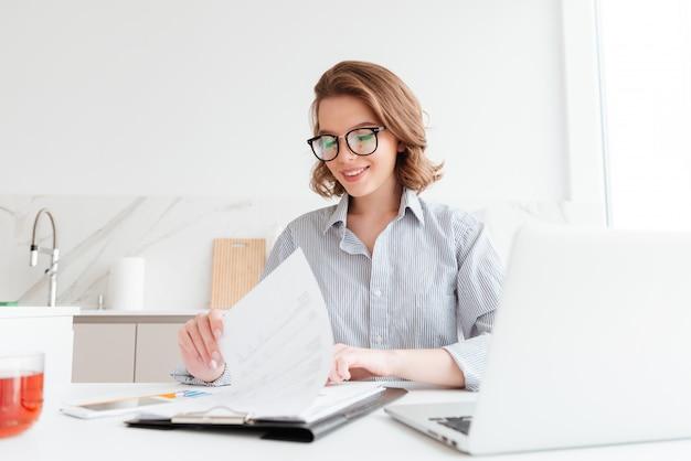 부엌에서 일하는 동안 새로운 계약을 읽고 안경에 쾌활 한 여자 무료 사진