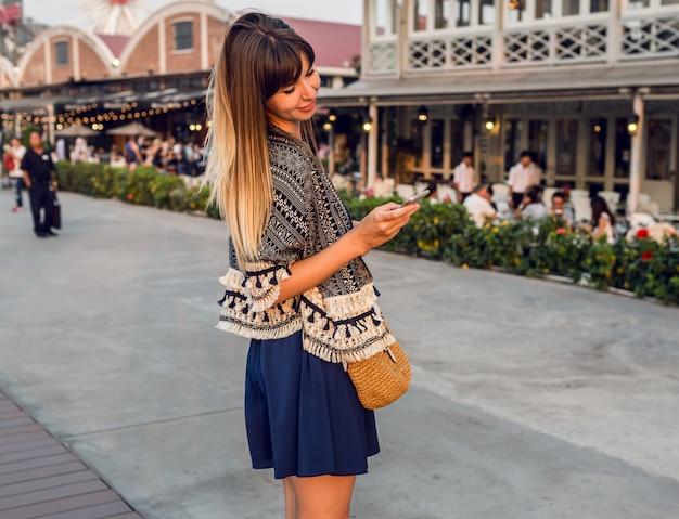 Веселая женщина в стильном наряде разговаривает по мобильному телефону и улыбается на набережной в бангкоке Бесплатные Фотографии