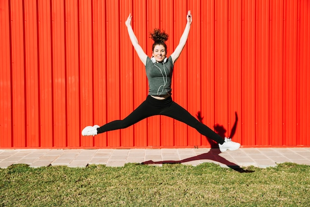 Cheerful woman jumping near red wall Free Photo