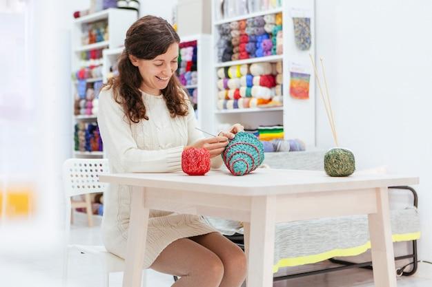 Cheerful woman knitting a christmas tree with woolen yarns Premium Photo