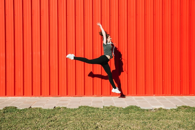 Cheerful woman leaping near red wall Free Photo
