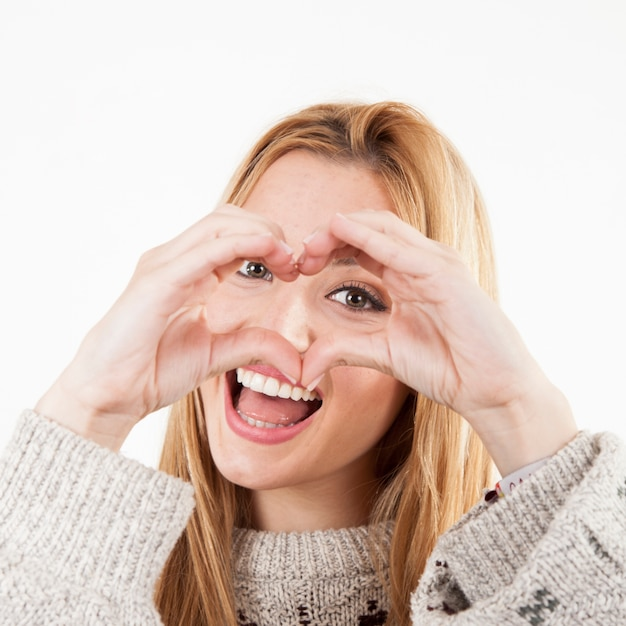 Cheerful woman making heart gesture Free Photo